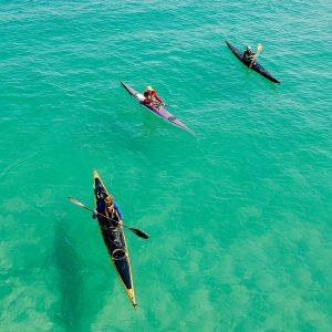 Drei Kajakfahrer im Wasser